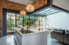 Refurbishment of a 3 storey townhouse in SW London featuring an eclectic industrial style kitchen with crittall windows