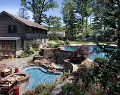Free form swimming pool with vanishing edge, with a 6' waterfall, overlooking an oversize heated spa, 3 burner built-in fire pit, Large outdoor custom kitchen and Bar area, and large natural stone patios