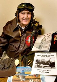 Bob Armstrong wears his flying gear as he talks about piloting B-17 heavy bombers during fighting in World War II. The Topekan is holding a book based on his wartime diary. (+)
