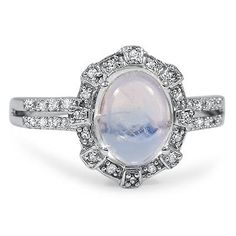 This spectacular ring showcases a gorgeous oval cabochon moonstone within a sparkling diamond halo and a decadent double row diamond accented band. Magnificent and very distinctive, this Modern Estate piece is a showstopper (approx. 0.16 total carat weight).