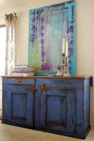 Heavy scaled piece in weathered blue finish is good in an earthy room. Traditional paintings  and folk art are choices for a purely earthy space.  The surprise addition of an abstract painting shifts this to earthy/artsy.  Marie-Elise Larene - Google Search