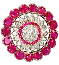 Wrapped in Red - Ruby Diamond Pendant, circa 1930. Luscious coloration and sheer dazzle is imbued in every millimeter of this Art Deco pendant of 14k white and yellow gold. Open work design aims for sophisticated style with bull's eye precision of seven (7) single cut diamonds and an inner circle of twenty (20) small rubies banded with yellow gold.
