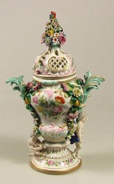 A 19th Century German porcelain two handled pot pourri vase and cover in the rococo manner, the urn shaped body enamelled in colours with floral sprays and encrusted with flowers, the pierced domed cover with floral finial and supported by two figures of putti, 13.5ins high (crossed swords type mark in underglazed blue to base - slightly chipped and damaged)