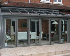 photo of traditional grey breckenridge conservatory with folding sliding doors and patio