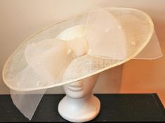 This is a stunning handmade fascinator hat, which is made with 3 layers of good quality sinamay in ivory. Other colours are available.  The fascinator is decorated with a large spotted crinoline bow in ivory and elastic is attached to enable you to fix the fascinator to your head.  The fascinator is presented in a lovely black and white hat box, which is ideal for storage!  This item would be perfect for a wedding or a day out at the races!  Dimensions: 45 cm x 36 cm
