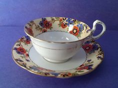 Here is a whimsical teacup and saucer made by Aynsley with a blue and rust floral border as the focal point of its design. Pretty blue and rust flowers are overlayed on a cream background border on both the cup and the saucer. The handle, base and rims are trimmed in gold gilt. The teacup set is in good vintage condition with no chips, cracks or crazing. There is some wear on the gold gilt of the handle. Measurements Cup Width: 3 3/4(9.5cm) Height: 2 1/2(6.5cm) Saucer Width: 5 1&#x...