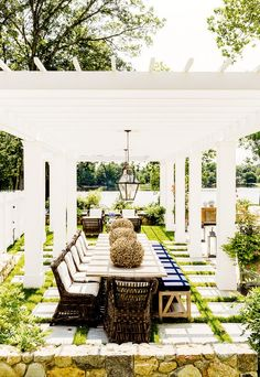 This traditional patio takes full advantage of its waterfront locale by placing the dining area mere feet from the shore. The white pergola adds architectural interest and definition and enables the incorporation of light fixtures—both of which make the eating area feel more like a dining room than a backyard.