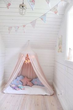 perfect little girl room with white shiplap, wooden floors, pink tent and floral bunting