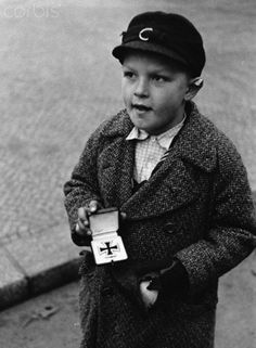 historicaltimes:  A German boy tries to sell his father's Iron Cross for cigarettes, Berlin, 1945 via reddit