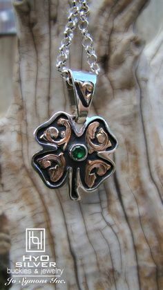 Lucky you! This sterling silver clover pendant is embellished with yellow gold fill scrolls and an emerald green crystal bezel set in the center. Black background antique adds contrast the the brilliant hues of silver and gold. Up your luck with this Hyo favorite! PN039, $195.