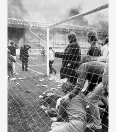 Football fans take refuge in the goal area as the devastating blaze rages through Bradford City's Valley Parade football ground.