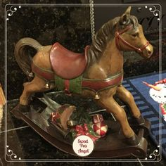 This is our wooden Christmas rocking horse. It has a Christmas tree and presents underneath the horse!