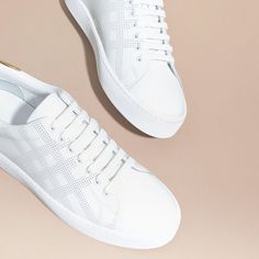 Smooth leather trainers designed with a perforated check. A cushioned ankle cuff and tongue ensures a comfortable stride.
