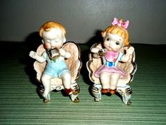 """Set of 2 vintage Ucago boy and girl sitting in chairs. The boy is drinking from his cup with only one shoe on. The girl is taking a bite with her spoon. Great gold trim on both. They measure 4.5"""" tall. No chips or cracks. Super cute! 