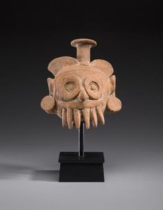 Aztec Head Fragment of a Diety, ca. A.D. 1470-1521 height 10 3/4in (27.3cm)  Depicting Tlaloc, god of rain, fertility, and water, the top of the head is shaped as the spout of a water vessel suggesting that it ornamented the top of a vessel that would have contained sacred water obtained from deep in mountain caves.