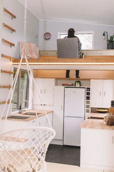 A wall ladder provides access to an office loft with built-in desk attached to the wall. A foot-well drops down to a shelf in the kitchen below to allow you to sit comfortably on the floor.