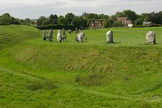 A view of part of the diameter earth ring and ditch surrounding some of the standing stones with Avebury village in the background. Stone Pictures, Stonehenge, England Uk, The Rock, Wales, Places To Travel, Places Ive Been, Postcards, Britain