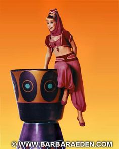 """A fun and rare shot of Barbara sitting on the lip of the giant bottle prop used in """"I Dream of Jeannie."""""""