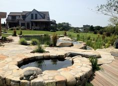 Lovely stone and wood deck around the natural pool becomes a hip hangout on hot summer days