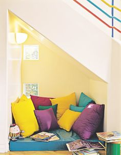 19 Clever Uses for the Space Under Your Stairs via Brit + Co.// Packed with pillows