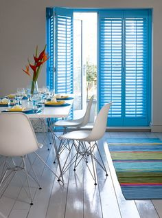 The use of bright colours on the shutters and rug, alongside the smooth, modern dining table create a truly contemporary look and feel.