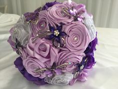 A popular flower bouquet of different shades of purple and lilac with some white flowers to balance it off. It is topped with very pretty brooches of flowers and dragonflies, and has a small fringe of types of thin ribbon.  All bouquets can be reproduced in the size and colour of your choice. Feel free to mix and match ideas to make your bouquet more individual. Corsage, MOB and Lapel pins are also available to match your colours. Contact leeann@bejewelledbridal.com.au for more information.