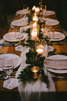 Rustic candlelit wedding reception centrepiece with foliage and chiffon table runner.