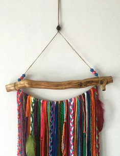 Lovely dream catcher style featuring a bohemian garland wall hanging mobile made from various colorful yarns in a variety of colors hanging from a dried and clean and varnished mountain pine tree root. The longest yarn hangs around 37 inches long from top of branch and 54 inches