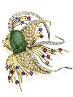 A gem-set tropical fish brooch The body of the fish set with an oval cabochon-cut nephrite, the fins and tail set throughout with single-cut diamonds, half pearls and circular-cut sapphires and rubies, width 44mm, the diamonds estimated to weigh approximately 0.25ct in total