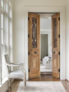 French hallway boasts a light gray French chair placed atop a faded rug in front of carved wood bi fold doors  Love the antique doors.