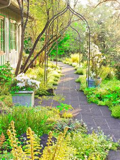 Incorporate winding paths into your landscape. Here, metal arbors draw the eye forward.