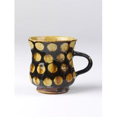 Staffordshire, c. 1700. Mug of buff-coloured earthenware; the inside is coated with white slip and the outside with brown over which are four rows of discs in white slip, the whole being covered with a yellow glaze. The lower portion rounded, wide spreading mouth, small loop handle.