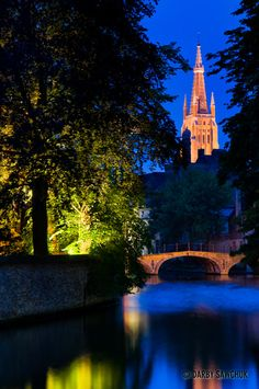 The Church of Our Lady behind a canal in Minnewater Park in Bruges, Belgium