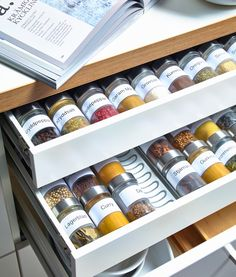 Close-up of an open kitchen drawer where clear glass spice jars lays on inserts.