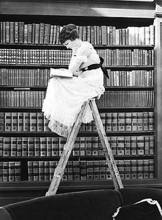 corbis images 1920's | 1920 Young woman perched atop a ladder in library, reading..