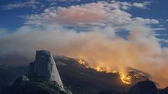 In this Sunday, Sept. 7, 2014, photo provided by Michael Frye, a wildfire burns next to Half Dome in Yosemite National Park, Calif. As of Monday, the fire has burned through about four square miles.