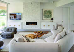 A simple, subdued color scheme, layered on a poured concrete floor, has a vintage Stephen Chase sofa as its inviting centerpiece. Split-face quartz sourced at Victory Tile & Marble gives the floating fireplace its sparkling, rock-candy look. A vintage 1960s painting plays nicely with the bronze horse from an Avignon, France, flea market that tops the floating credenza. Photo: David Blank for Desert Magazine