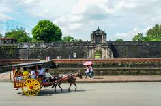 A horse-drawn carriage passes by the entrance to Fort Santiago