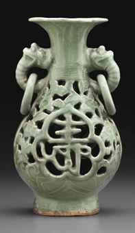 A RARE LONGQUAN CELADON OPENWORK PEAR-SHAPED DOUBLE VASE MING DYNASTY, CIRCA 1450-1550 The flattened, pear-shaped outer body surrounds an inner tubular body and has an openwork design of peony and camellia rising from rocks on either side of a shou character on one side and pomegranate and chrysanthemum rising from waves to flank a fu character on the reverse, below a band of key fret at the base of the neck ... 9 in. (23 cm.) high, stand SOLD for $16,250