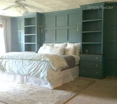 DIY built-ins using an Ikea Tarva Hack around a bed with wainscoting. I love how all the molding is painted the same color which is BM Blue Echo.