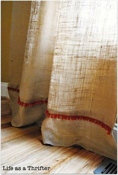 burlap curtains with pom pom fringe. too cute! Would be cute as cafe curtains too.