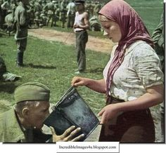 A Russian woman gives a German POW a drink of water near Kiev