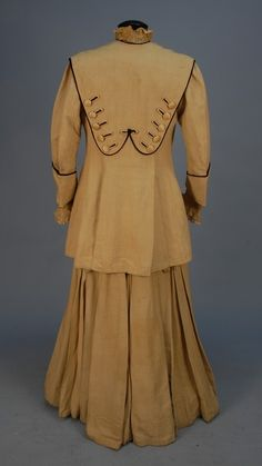HEAVY SILK WALKING SUIT with UNUSUAL TRIM, EARLY 20th C. Dress and jacket of natural ottoman lavishly trimmed with black piped scallops, 84 self buttons, blue Chinese figural embroidered silk. High neck dress having handmade bobbin lace undersleeves and bodice trim, black satin cummerbund, two large brass portrait buttons at back waist. Jacket with deep cuff, faux pockets, Chinese silk faux vest. Johnston Estate.