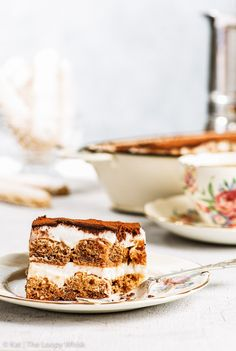 A slice of dairy and gluten free tiramisu, with a bite taken out of it, on a decorative antique plate with an antique fork. The dish with the rest of the tiramisu, a cup of coffee and more homemade gluten free ladyfingers are in the background.