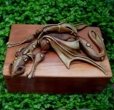 A handcrafted dragon is draped across a beautifully crafted box made from English yew.The box is 10cmx7cm
