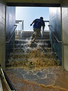 A member of the Kansas City Royals tarp crew bolts up the dugout steps to open a clogged drain as water pours in during Monday's storm that postponed the baseball game against the Tampa Bay Rays on July 6, 2015 at Kauffman Stadium in Kansas City, Mo.