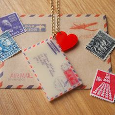 """Show your appreciation for the dying art of letter writing with this quirky love letter necklace.Vintage look printed acrylic Airmail envelope pendant with red heart shaped charm. The letter measures an eye-catching 5 cm long and is strung on an 18"""" gold plated chain."""