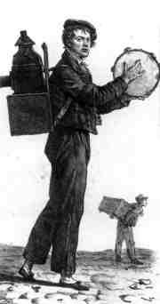 An early showman carries his magic-lantern and slides on his back.