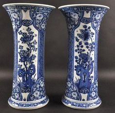 A GOOD PAIR OF 17TH CENTURY CHINESE BLUE AND WHITE VASES Kangxi, painted with flowering rock within panels of floral motifs. 15.5ins high.