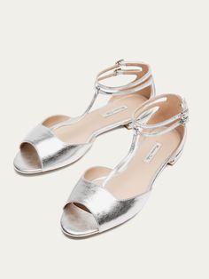 Bailarina de piel acabado laminado en color plata. Detalle de doble pulsera al tobillo con hebillas metálicas. Forro y planta en piel caprina.
